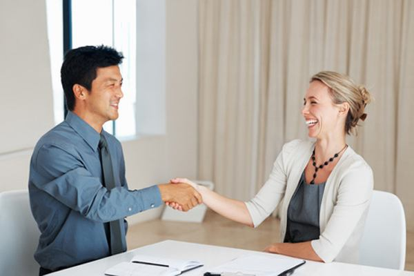 Two corporate partners shaking hands during meeting with colleague looking on